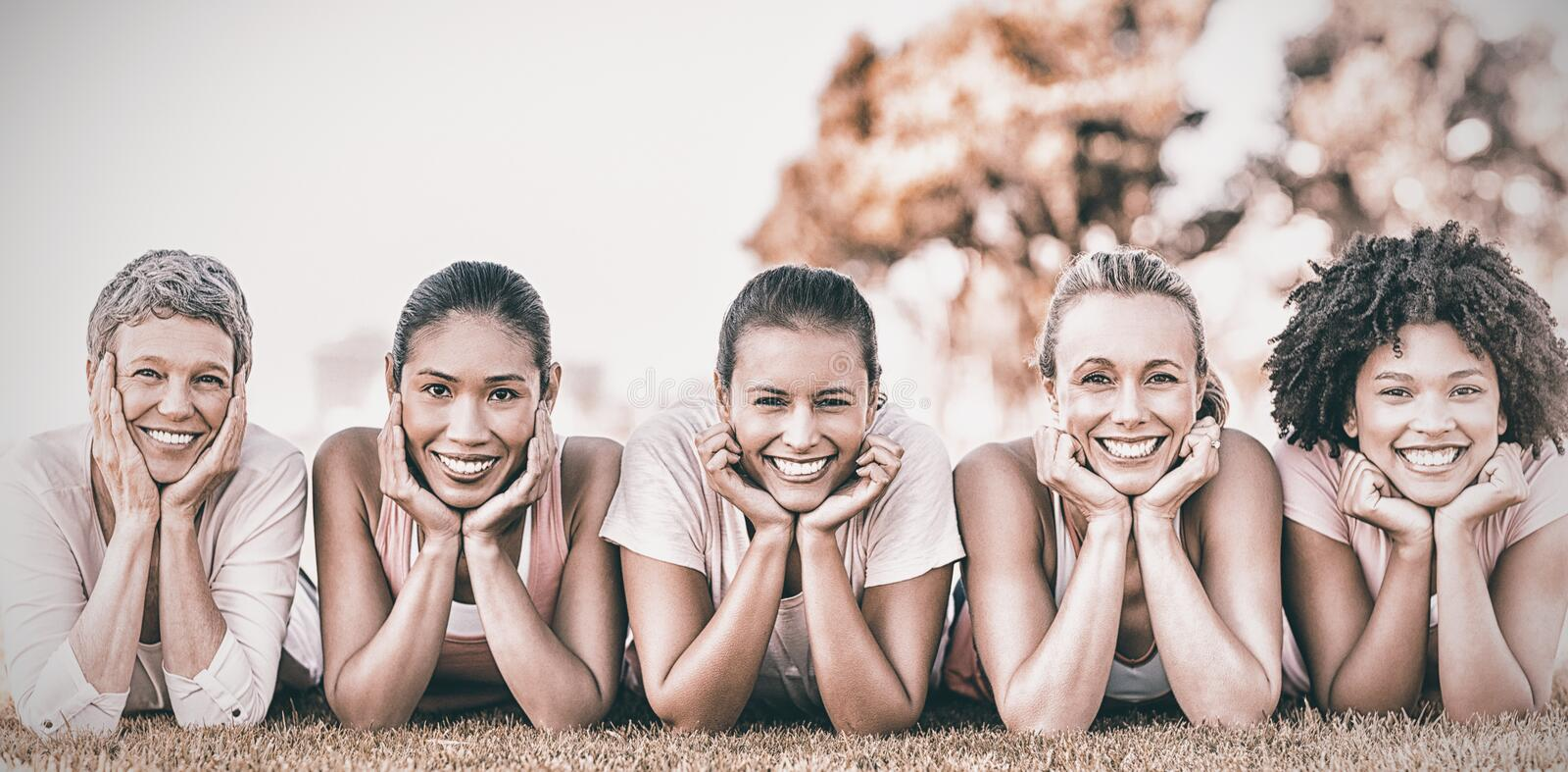 Smiling women lying in row for breast cancer awarness. Portrait of smiling women lying in a row for breast cancer awarness in park royalty free stock image