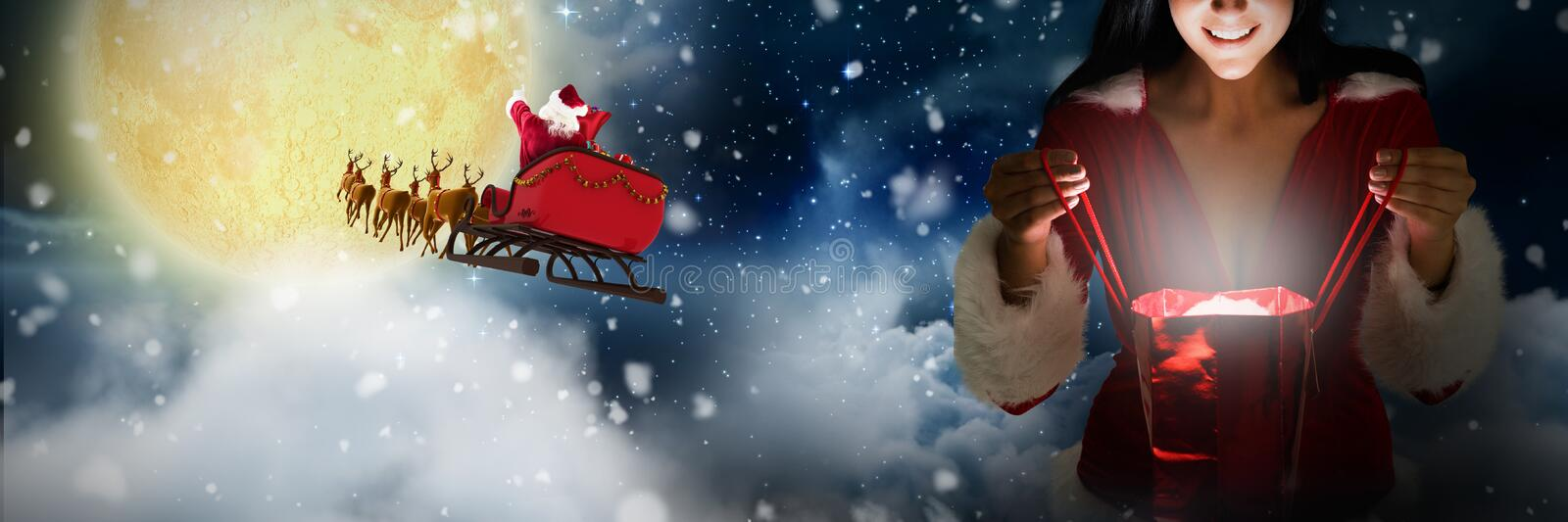 Composite image of smiling woman opening christmas present. Smiling women opening christmas present against stars twinkling in night sky royalty free stock images