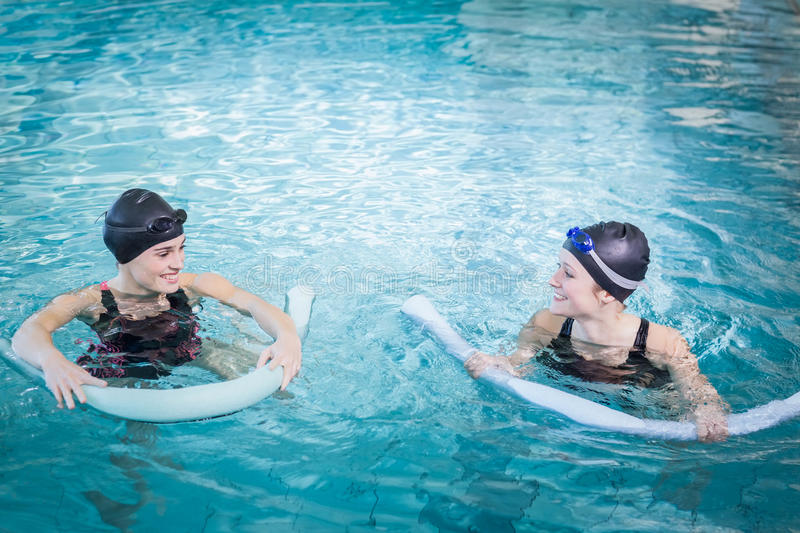 Smiling women in the pool with foam rollers royalty free stock photos