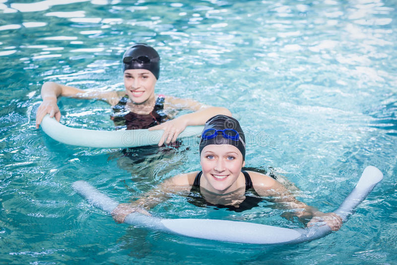 Smiling women in the pool with foam rollers royalty free stock photo
