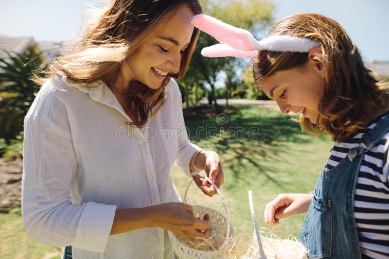 Happy mother and daughter putting sweets in baskets royalty free stock photography