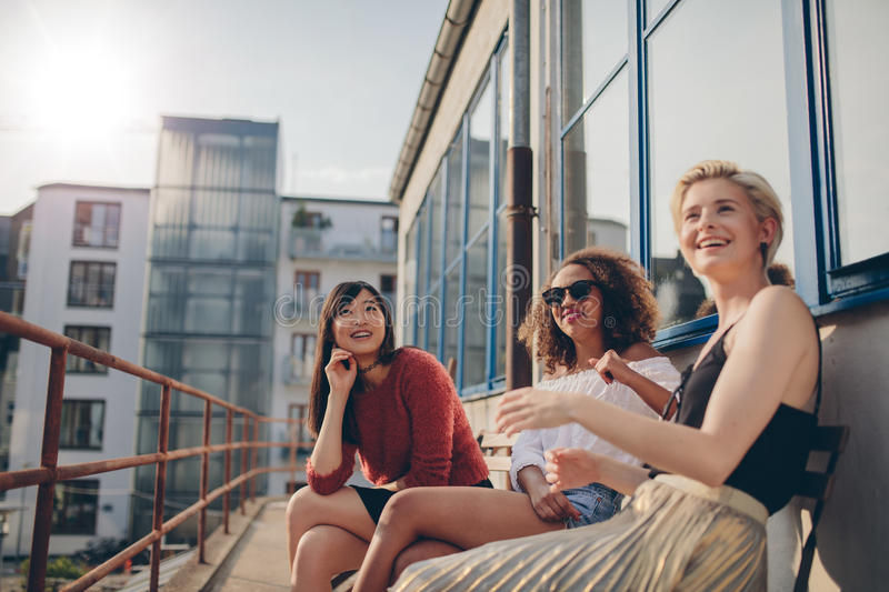 Smiling women relaxing outdoors in terrace. Happy three young female friends sitting in balcony and smiling. Women relaxing outdoors in terrace stock photo
