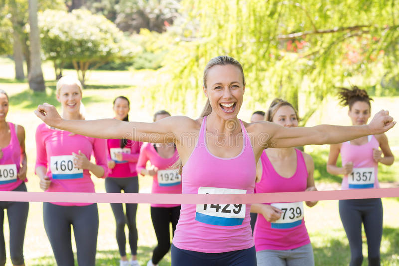 Smiling women running for breast cancer awareness. On a sunny day royalty free stock image