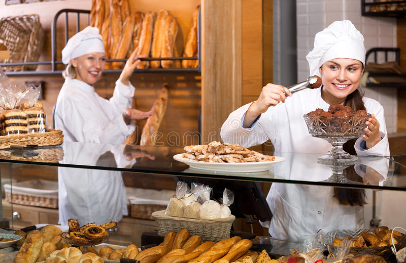 Smiling women selling fresh pastry and loaves. Positive women selling fresh pastry and loaves in bread section. Focus on the young woman royalty free stock photo