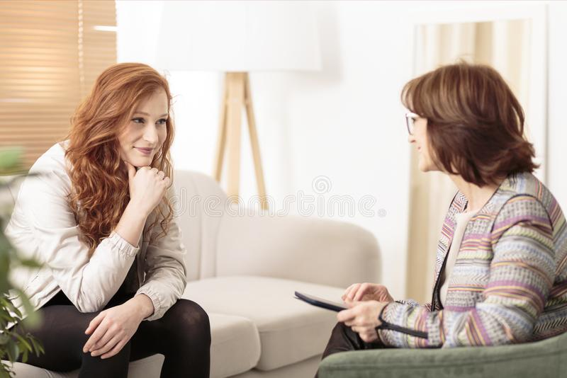 Smiling woman and wellness coach. Smiling women talking to a wellness coach to find motivation to achieve physical health goals stock photos