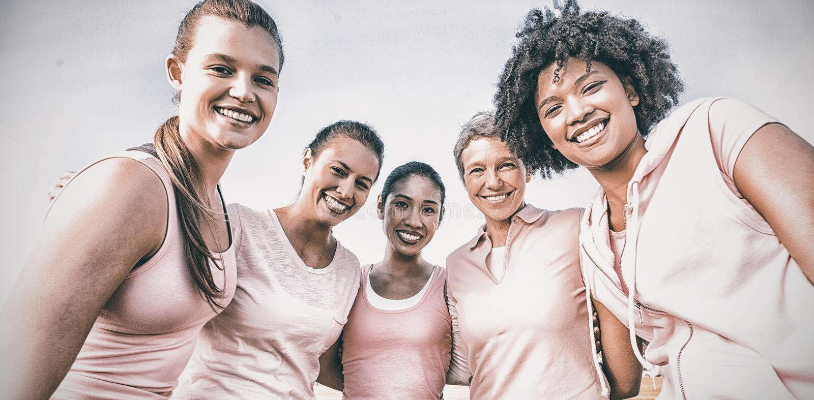 Smiling women wearing pink for breast cancer. Portrait of smiling women wearing pink for breast cancer at park royalty free stock image