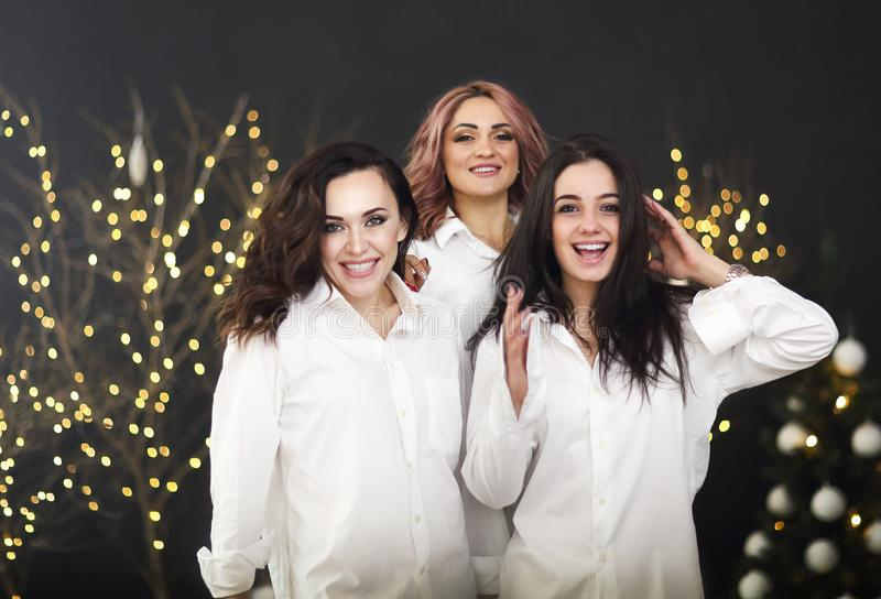 Smiling women in white shits with glasses of champagne over lights background royalty free stock photography
