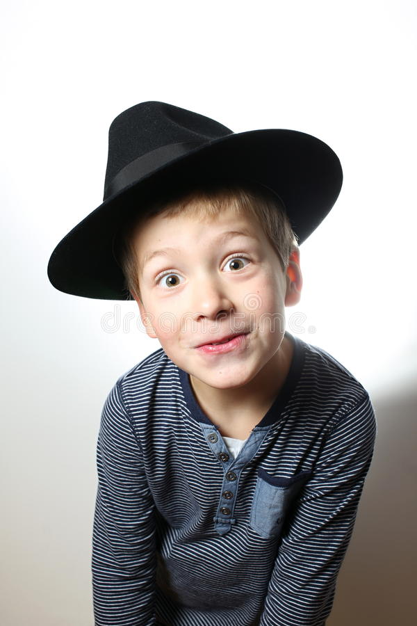 Smiling and wonderstruck boy in the black hat stock photo
