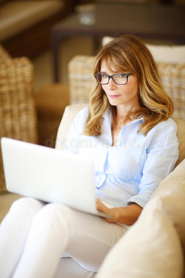 Smiling wooman with laptop at home. Close-up portrait of casual businesswoman woman using her laptop while working at home stock photos