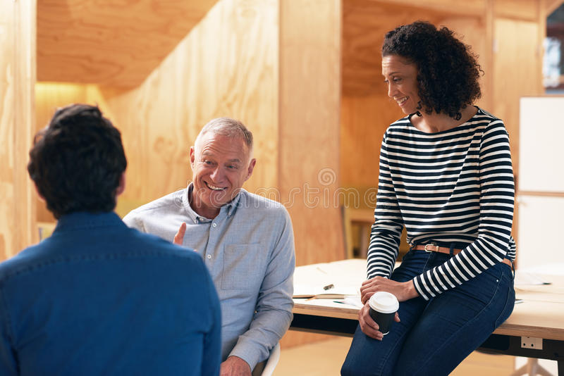 Smiling work colleagues talking together in an office stock photo