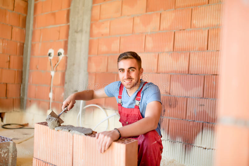 Smiling worker building brick walls with cement, mortar and putty knife. Mason using mortar for building walls. Smiling worker building brick walls with cement royalty free stock images