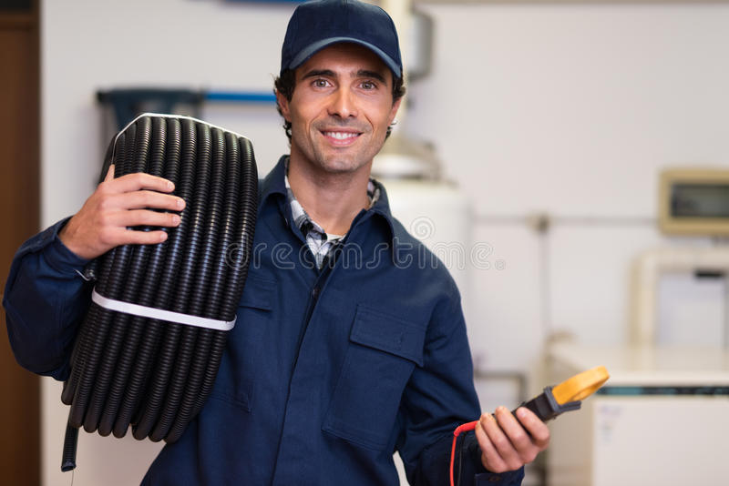 Smiling worker carrying corrugated conduit and a tester royalty free stock photos