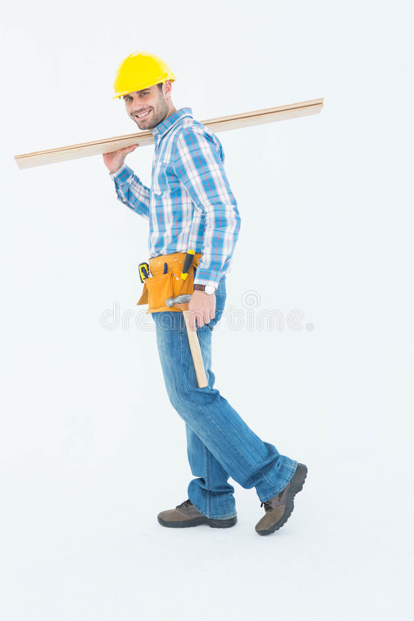 Smiling worker carrying wooden planks royalty free stock image