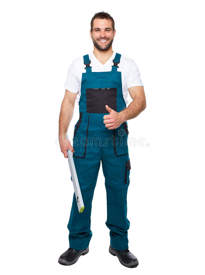 Smiling worker in green uniform with spirit level stock photography