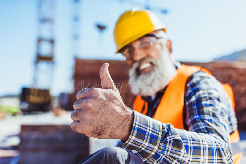 Smiling worker in reflective vest and hardhat sitting at construction site and showing stock photo