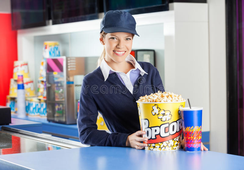 Smiling Worker With Snacks At Cinema Concession. Portrait of smiling worker with popcorn bucket and drink at cinema concession counter stock photography