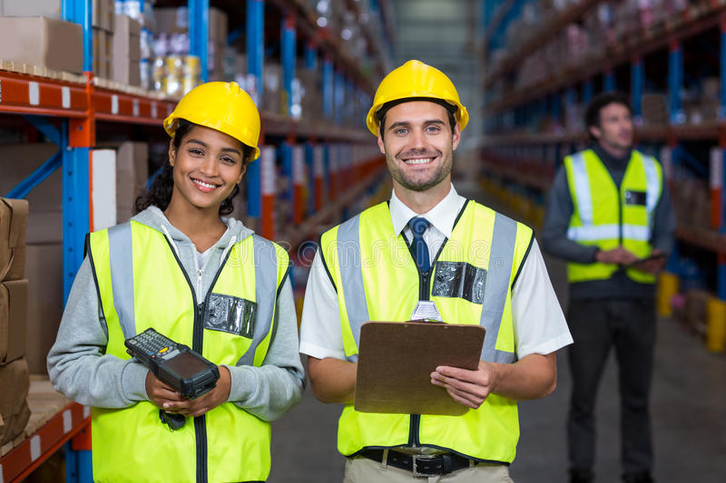 Smiling worker wearing yellow safety vest looking at camera. In warehouse royalty free stock photography