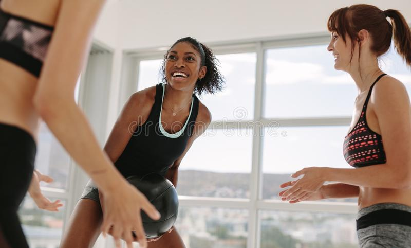 Smiling workout partners exercising with medicine ball. At fitness gym. Multiracial women working out with fitness ball royalty free stock photography