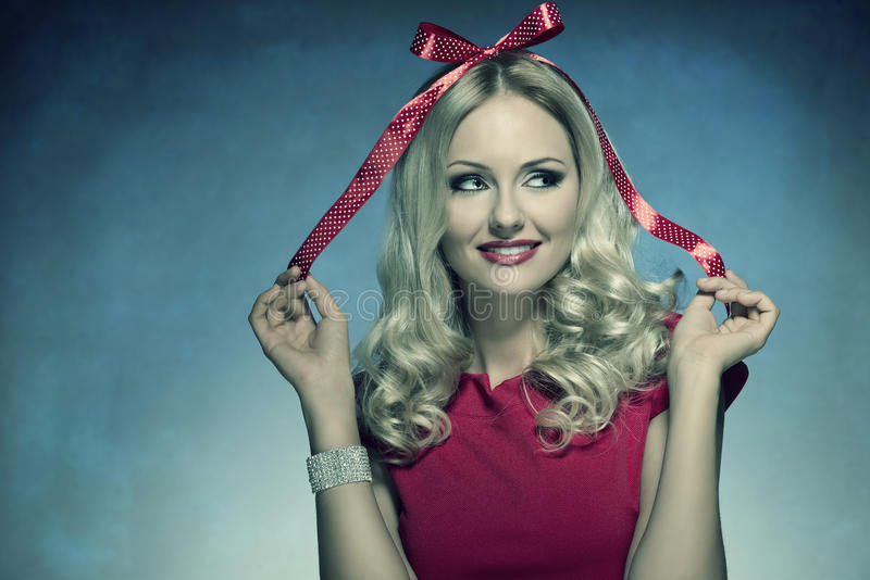 Smiling xmas woman with bow. Close-up funny portrait of cute blonde girl with xmas bow on her head like a gift, wearing red elegant dress and bright bracelet royalty free stock images