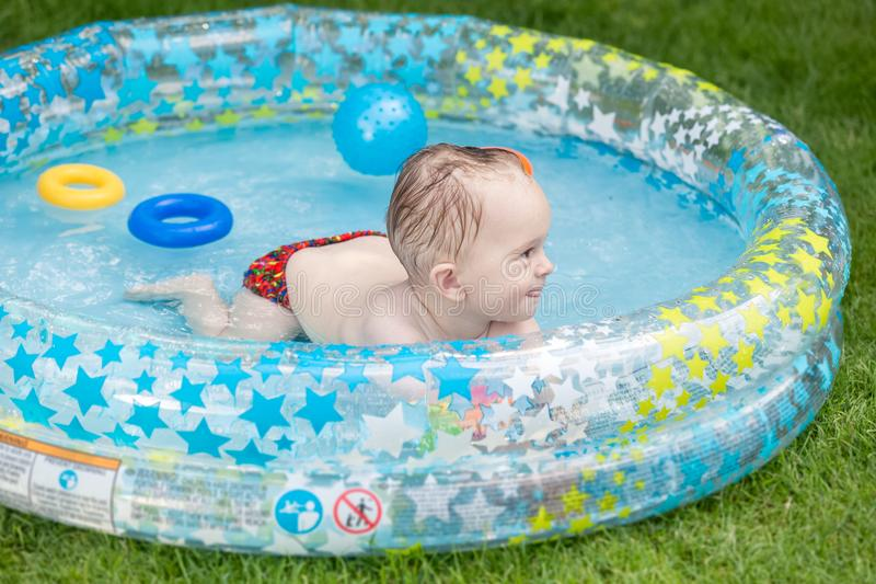 Portrait of smiling 1 year olf baby boy swimming in inflatable swimming pool at house backyard. Smiling 1 year olf baby boy swimming in inflatable swimming pool royalty free stock photo