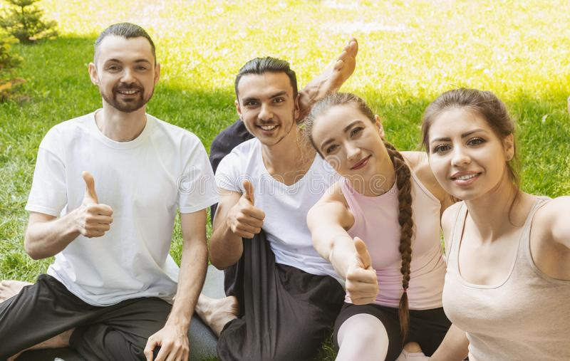 Smiling yoga students showing thumbs up after practicing. stock photo