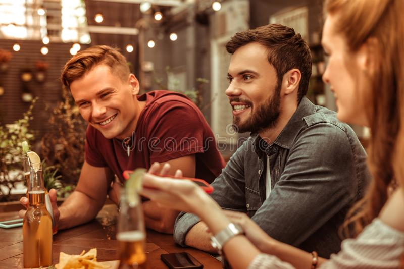 Smiling young-adult two men sitting at the bar table. Smiling men. Smiling beaming attractive happy stylish young-adult two men sitting at the bar table stock photos