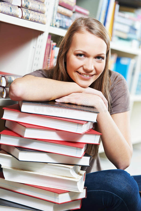 Download Smiling Young Adult Woman Reading  Book In Library Royalty Free Stock Image - Image: 23050366