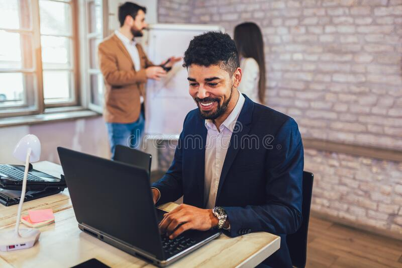 Young African American businessman working online with a laptop while sitting at his desk in a modern office stock images