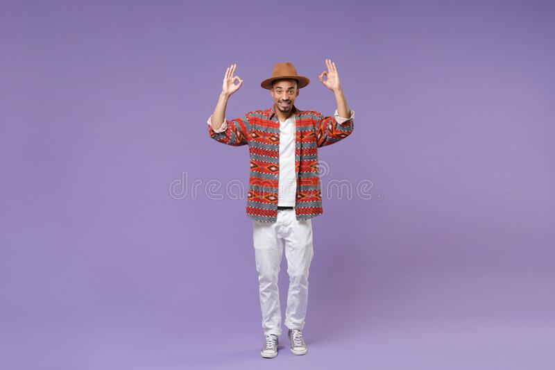 Smiling young african american guy in casual colorful shirt hat posing isolated on violet background studio portrait royalty free stock image