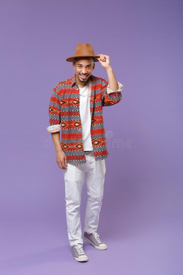 Smiling young african american guy in casual colorful shirt hat posing isolated on violet background studio portrait royalty free stock images