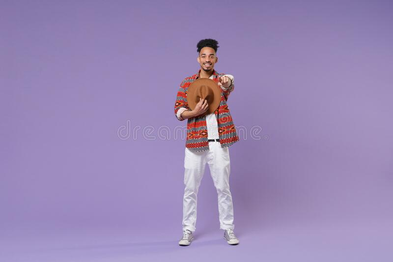 Smiling young african american guy in casual colorful shirt posing isolated on violet background studio portrait. People royalty free stock photography