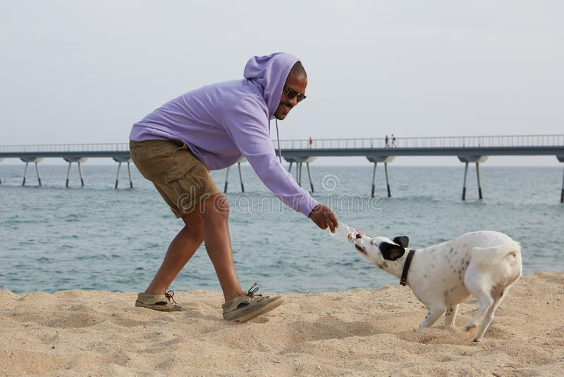 Smiling young African-American man hipster in sport hoody playing with his dog on the beach at sunny day. royalty free stock photo