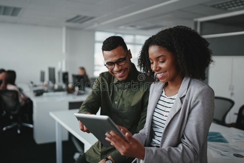 Smiling young african american professional businessman and businesswoman together working online with a digital tablet royalty free stock photo