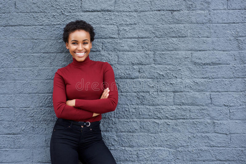 Smiling young african american woman against gray wall stock photo