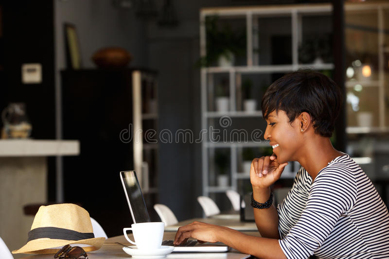 Smiling young african american woman working on laptop royalty free stock image