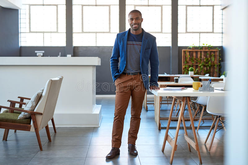 Smiling young African businessman standing confidently in a modern office stock images