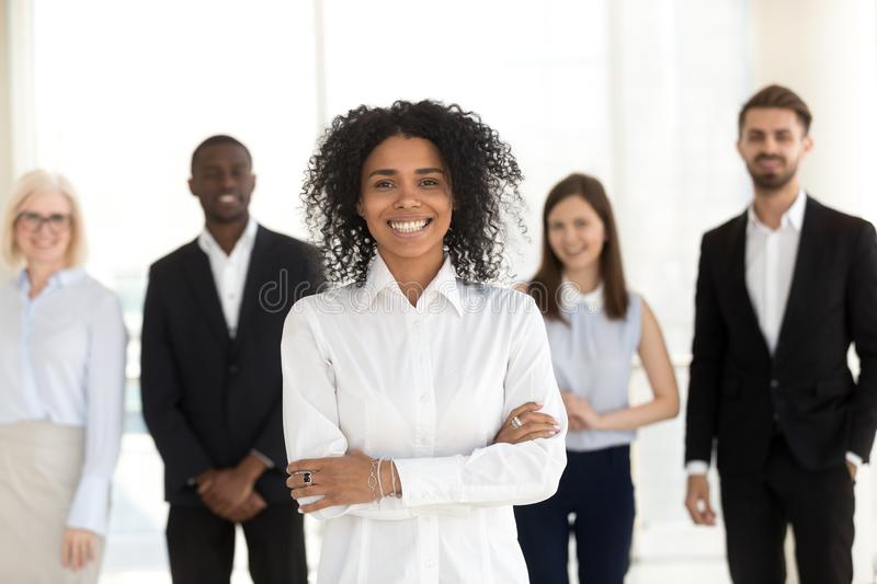Smiling african employee standing with diverse team in office, p royalty free stock photography