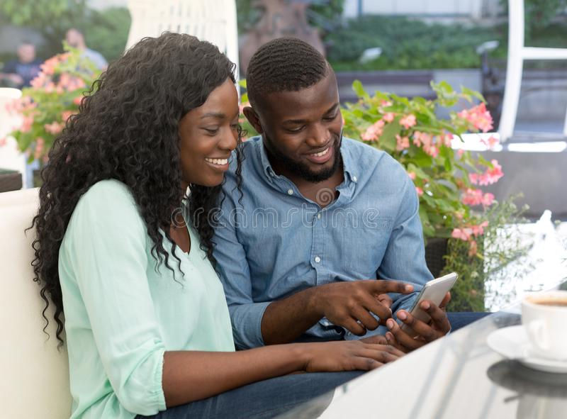 Smiling young african couple having fun looking at smartphone in cafe terrace stock image