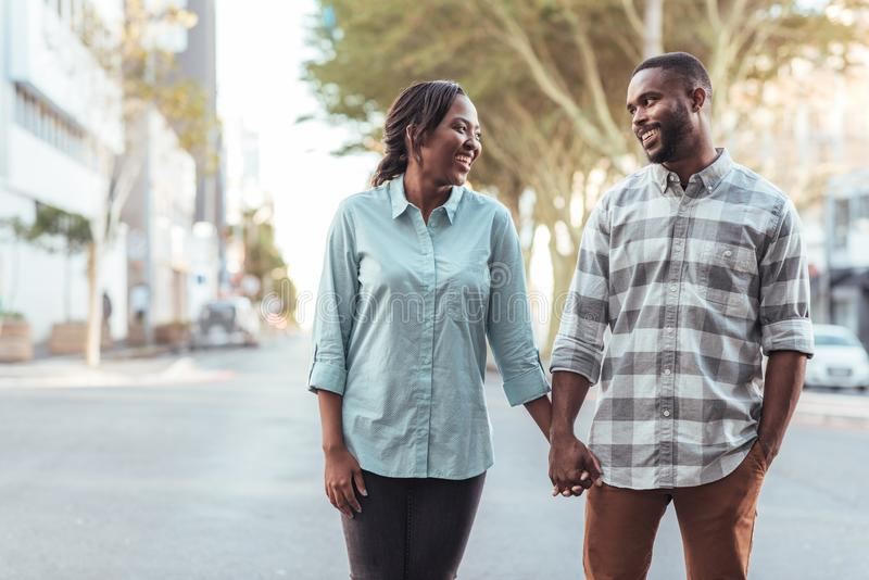 Smiling young African couple holding hands in the city together royalty free stock photo