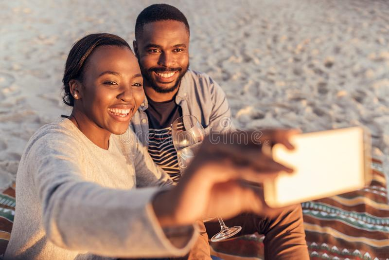 Smiling African couple sitting together at the beach taking selfies stock images