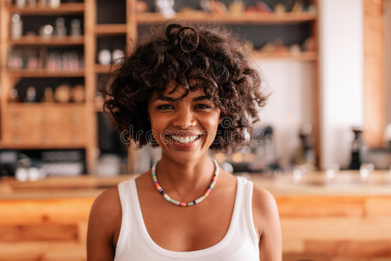 Smiling young african female in a coffee shop royalty free stock images