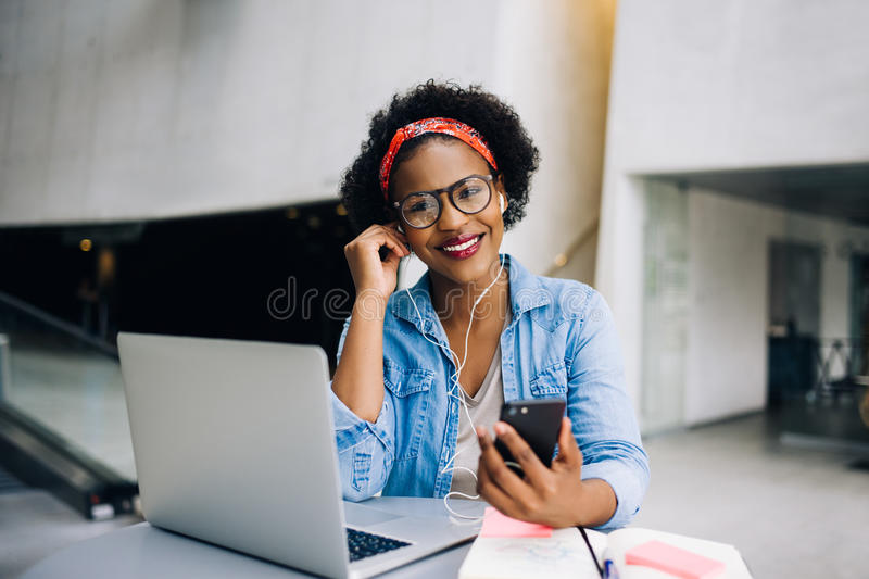 Smiling young African female entrepreneur working and listening royalty free stock images