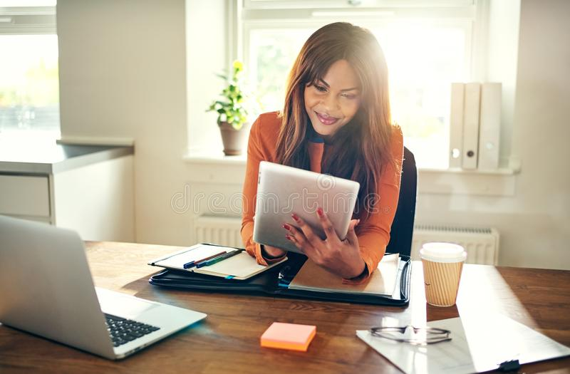 Smiling woman working with a tablet in her home office royalty free stock photo