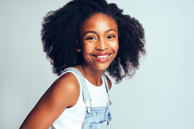 Smiling little African girl wearing dungarees against a gray bac royalty free stock photography