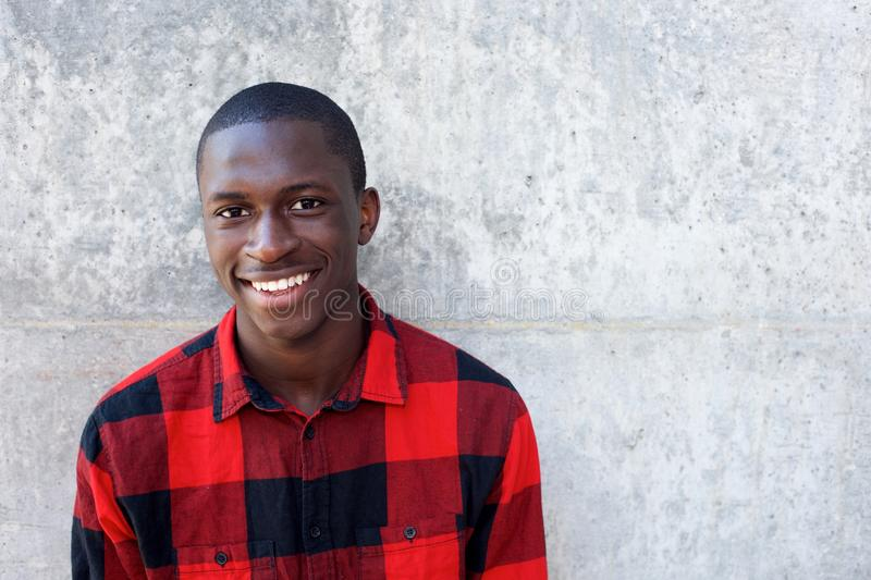 Smiling young african male model standing against wall royalty free stock photography