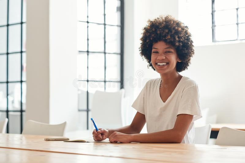 Smiling young African student studying alone at a campus table royalty free stock photo
