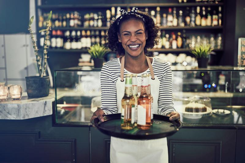 Smiling young African waitress holding a tray of drinks stock photo