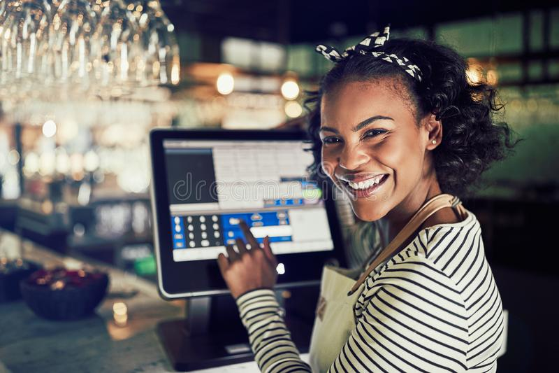 Smiling African waitress using a restaurant point of sale termin royalty free stock photography