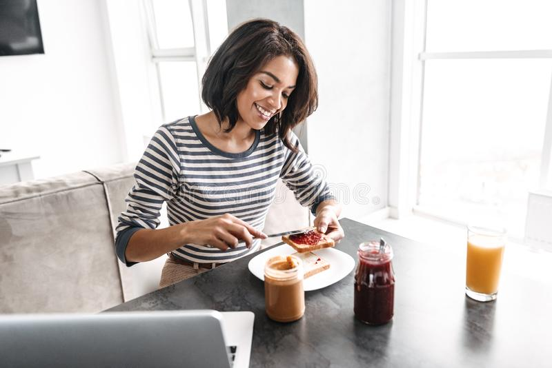 Smiling young african woman having breakfast. While sitting at the kitchen with laptop computer royalty free stock photo