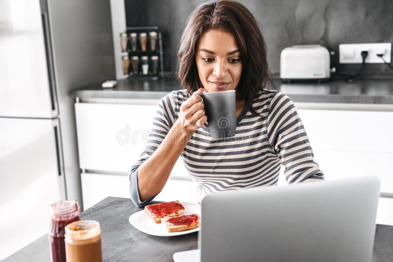 Smiling young african woman having breakfast. While sitting at the kitchen with laptop computer royalty free stock image